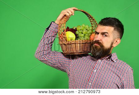 Farmer With Suspicious Face Presents Apples, Grapes And Cranberries.