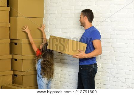 Girl and man with busy faces on white brick wall background. Daughter puts hands up and father puts boxes in pile. Accommodation moving and family concept. Kid and guy move into new home or move out