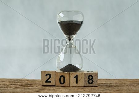 new year 2018 minimal concept as number 2018 wooden cube block with sandglass on wooden table and white background.