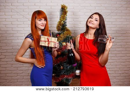 Two Beautiful Women In Evening Wear Partying With A Gift Box, Glasses And A Bottle Of Champagne Near