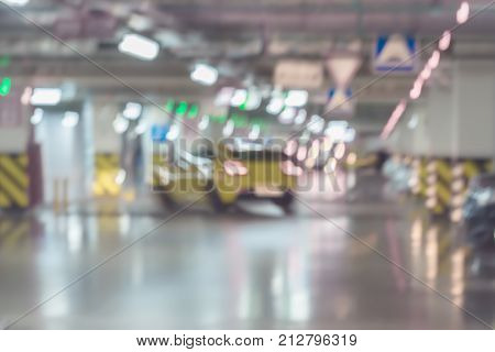 Abstract blurred car parking, garage, interior of underground parking with moving cars in building of shopping mall. With place for your text, for Defocused background, backdrop