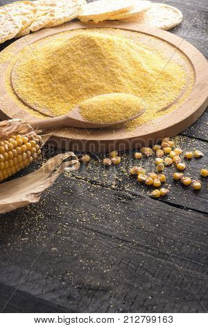 Corn flour on wooden board and grains - Vertical image with a pile of corn flour on a wooden board a corn cob and grains puffed corn cakes in the background on a rustic wooden table.