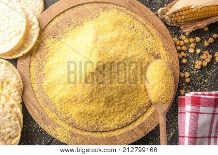 Corn flour and puffed corn cakes - High angle view image with a pile of corn flour on a round wooden board surrounded by corn cob grains and puffed corn cakes on a black wooden table.