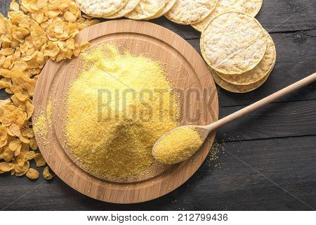 Corn products and flour on black table - High angle view of a round wooden board full of corn flour surrounded by products made of it corn flakes and puffed corn cakes on a black wooden table.
