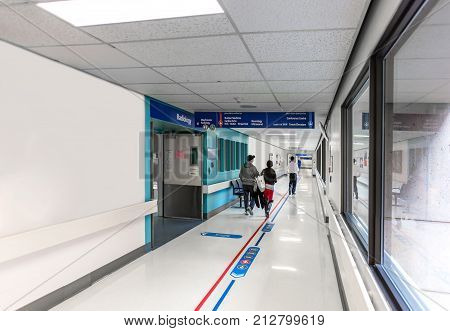 The patients urgently walking along the corridor of the hospital. A long corridor of a medical hospital with the effect of motion blurring the sides of the corridor and signs of a red medical cross information signboard and people walking in the distance poster