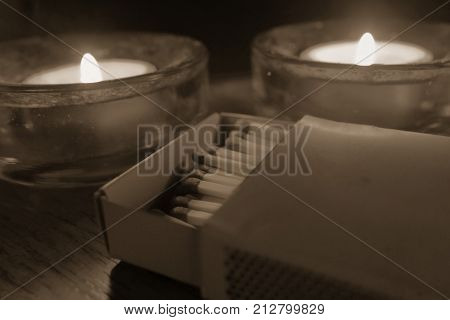 Matches. Matches in a box on a wood table with some candles behind.