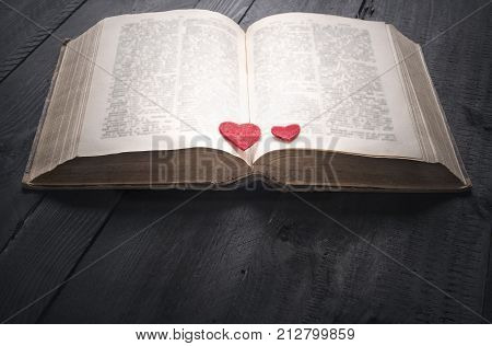 Two red hearts on an open book - Antique open book with two red hearts on its pages sitting on a black wooden background. A concept for the love of reading learning education or as a love story.