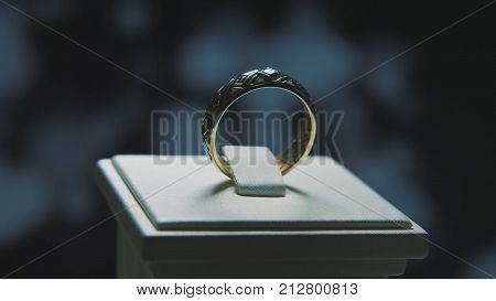 Golden finger ring with yellow precious stone. Ring in gold with sapphires browm, wedding ring - jewelery with diamonds and precious gems black background.