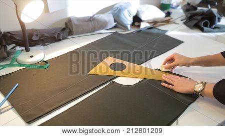 Female tailor stitching material at workplace. Preparing fabric for clothes making. Tailoring, garment industry, fashion designer sketch drawing costume concept and tailor draws sketches.