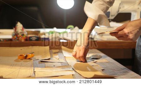 Female tailor stitching material at workplace. Preparing fabric for clothes making. Tailoring, garment industry, fashion designer sketch drawing costume concept and tailor draws sketches. Designer workshop concept. Tailor At Work In Small Business