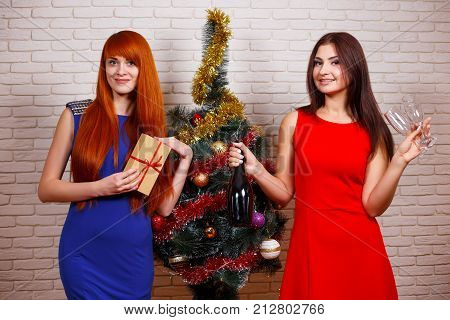 Two Beautiful Women In Evening Wear Partying With A Gift Box And A Bottle Of Champagne Near Christma