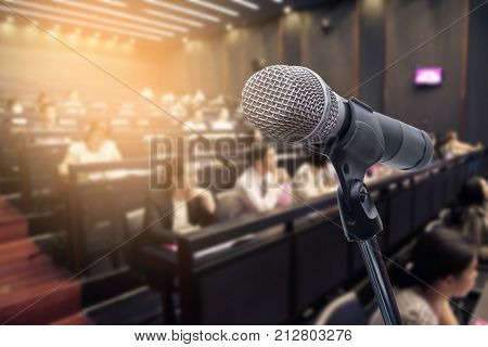 Microphone over the blurred business people forum Meeting Conference Training Learning or Coaching Concept Blurred background