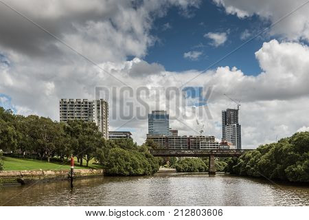 Parramatta Australia - March 24 2017: Approaching the city on the river looking at Macarthur Street bridge and tall office buildings all under heavy cloudscape. Green shores.