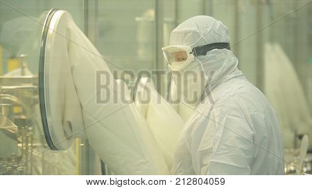 Pharmaceutical industry. Male factory worker inspecting quality of pills packaging in pharmaceutical factory. Automatic tape to create packaging and filling of medicines. control in the factory of medicine HD