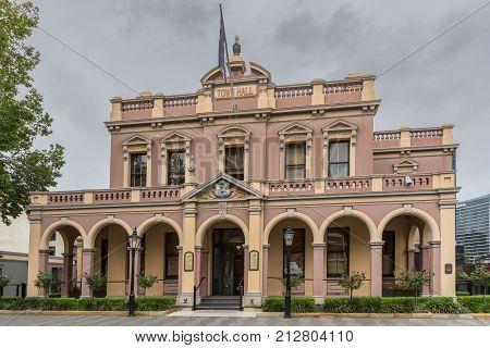 Parramatta Australia - March 24 2017: Brown historic Town Hall building under heavy rainy sky. Lanterns and green vegetation around.
