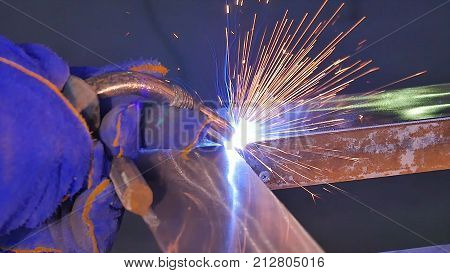 Metal Welding with sparks and smoke. Worker with protective mask welding metal. Welder joins metal parts. A process using a semi-automatic welding. Welding steel. Industrial Worker at the factory welding closeup.