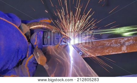 Metal Welding with sparks and smoke. Worker with protective mask welding metal. Welder joins metal parts. A process using a semi-automatic welding. Welding steel. Industrial Worker at the factory welding closeup. Industrial welding automotive.