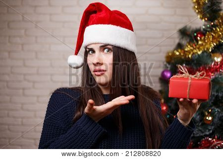 Young Cute Displeased Woman In Santa Cap Is Disappointed With Her Present. New Year, Christmas, Gift