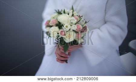 bride with flowers in hand outdoors in summer or winter. The bride is nervous before the wedding. Bride holding a perfume. nice wedding bouquet in bride's hand. Girl is holding beautiful bright wedding bouquet. the bride holding wedding bouquet of pink an