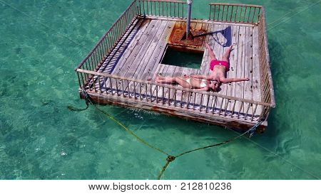 2 young people couple romantic sunbathing on pontoon with aerial view in beautiful clear aqua blue sea water
