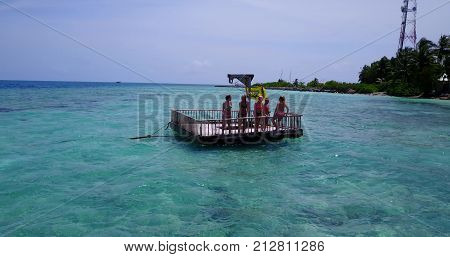 group of young beautiful girls sunbathing on pontoon with drone aerial flying view in aqua blue clear sea water and sky