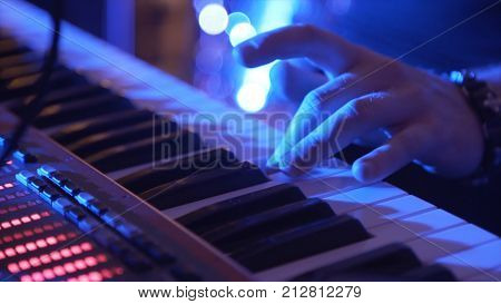 Closeup Of Male Hands Playing Piano. Man Playing The Synthesizer Keyboard. Man Plays Music Keyboard.