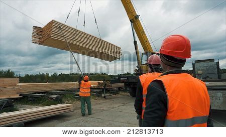 Worker in a construction site transporting a wooden bars using crane. Workers are used wooden ladder at construction site. Reinforced steel bars are protruding from the concrete pillar, base for new edifice. Transporting. Bonding of wooden bars.