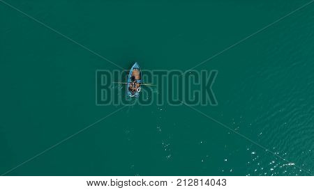 Aerial Boat on the lake. Aerial view on two men in a boat on a lake, rowed to the shore. Lonely boat in the middle of the river, lake. Boat single row on sea with reflection in the water in the morning light. Single Row boat on Lake with Reflection in the