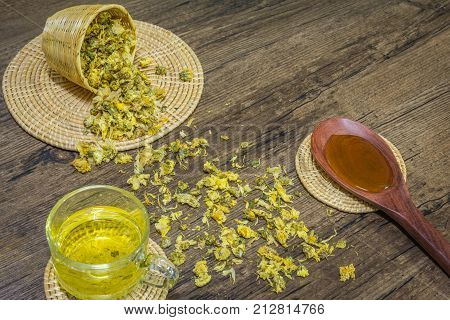 Chrysanthemum tea and honey bee on wood background Extend the arteries at the heart. Help prevent artery diseases such as hypertension angina.It absorbs