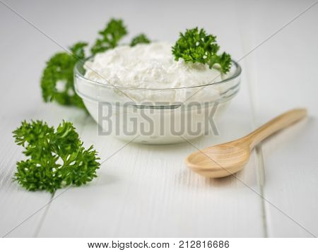 Curly leaves of parsley and a bowl of curd cream on a white table. The concept of a healthy diet. Curd cream