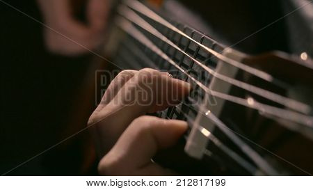 Practicing in playing guitar. Handsome young men playing guitar. Play the guitar. Hands playing guitar in diagonal position