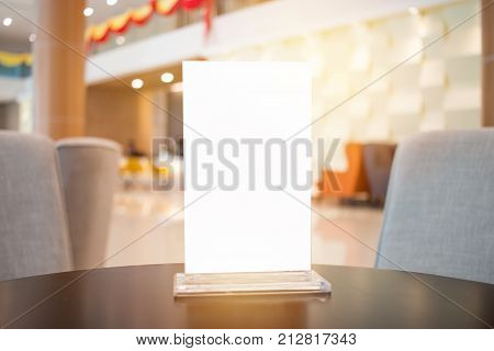 Mock up white Label for blank menu frame in Bar restaurant cafe. Stand for booklets with sheets paper tent card on table cafeteria blurred background insert for text of customer. Space for texting.