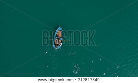 Aerial Boat on the lake. Aerial view on two men in a boat on a lake, rowed to the shore. Lonely boat in the middle of the river, lake. Boat single row on sea with reflection in the water in the morning light.