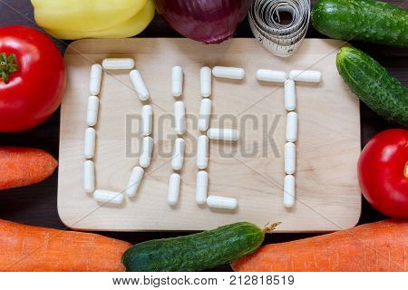 Fresh Organic Vegetables With Measuring Tape And Word Diet Made Of Pills On Wooden Board Background,
