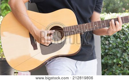 Guitar with a man's hands playing the guitar. man's hands plating acoustic guitar.