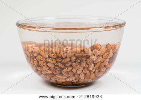 Dried orange coloured beans absorb water as they soak overnight to rehydrate.