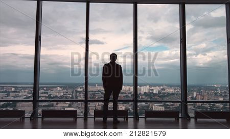 Rear view of man in formal suites who stand in front of panoramic window with city view. a man stands in front of big panoramic wiindow view from back HD