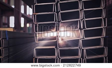 Metal pipe profile and sun in the background. Sheet metal profiles transporting, close up. Metal or aluminum profile channel for use in structures, warehouse. Bent metal profile channel. Factory HD