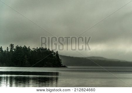 Canada Ontario Lake two rivers grey morning dark atmosphere little pinetree island on water in Algonquin National Park