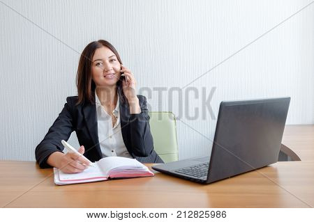 cute young office worker talking on cell phone in office.