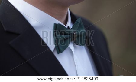 Close-up on nerd, man in bow tie. Man's hands touches bow-tie on a suit or tuxedo. man in a shirt and bow tie closeup