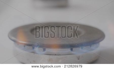 Burning gas plate on home kitchen stove. Modern Gas Stove Plate. Gas burner close up on home plate steel color.