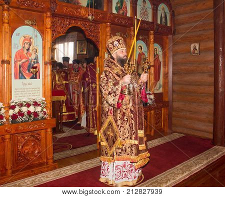 Adygea Russia - November 8 2017: the Archbishop with burning wax candles at the divine Liturgy in the Orthodox Church