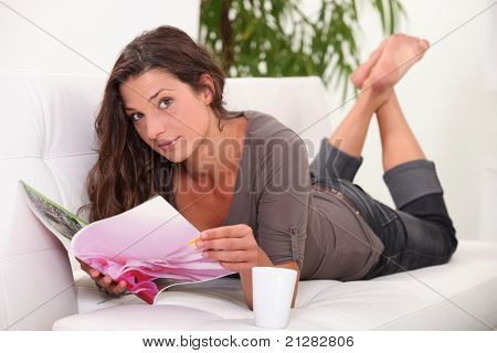 young woman lying down on a couch is reading a magazine