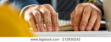 Male arms in suit typing on silver keyboard using computer pc at office workplace closeup. Accountant finger job modern lifestyle web search assistant enter account login password and note credential