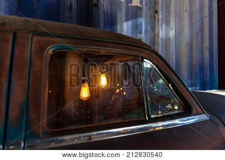 Edison Light bulbs in a vintage rusty car used as decoration/ Sectioned rusty car with Edison light bulbs used as decoration