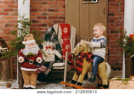 Playful Happy Cute Little Child Boy Dressed In Sweater And Jeans Sitting On Rocking Horse In Decorat