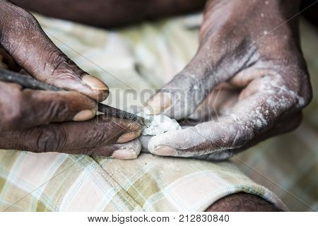 Close up of senior indian asian man sculptor carver hands working on his marble sculpture in his workshop with chisel.