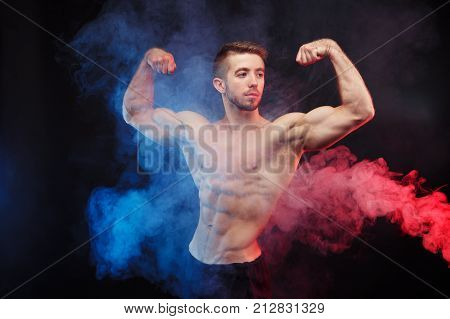 Bodybuilder Man With Perfect Abs, Shoulders,biceps, Triceps And Chest Flexing His Muscles In Blue An