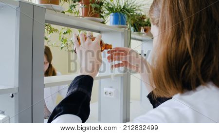 Serious science student pouring liquid in an test tube. Young woman pouring liquid into test tube.